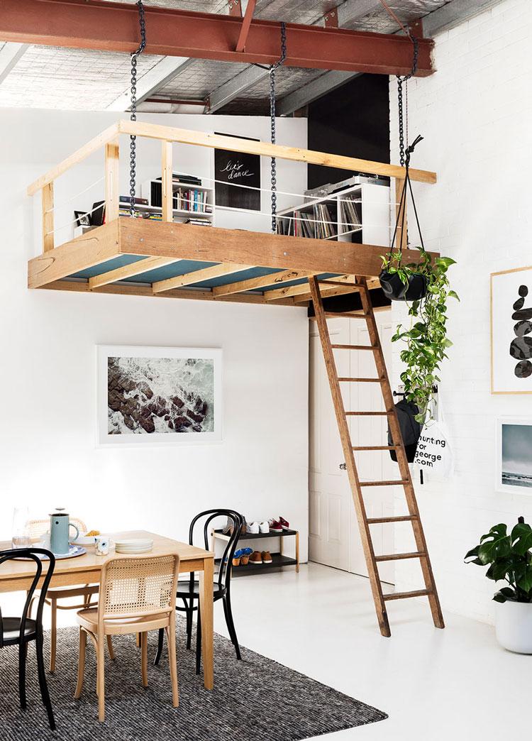 Une mezzanine en bois suspendue au dessus de la salle à manger